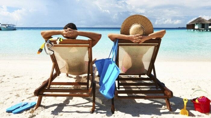 summer time couple on the beach relaxing and sunbathing woman with sun hat