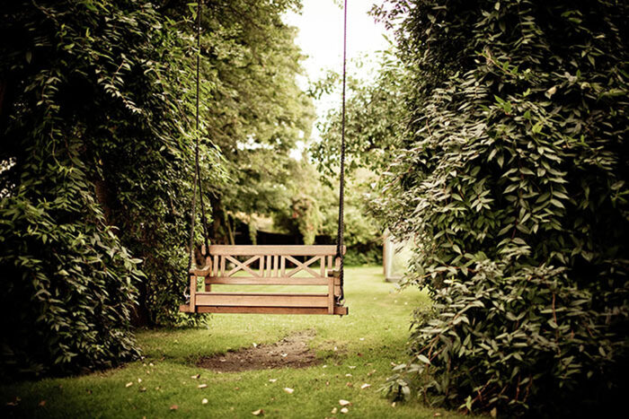 swing bench in a green garden with bushes and trees on both sides