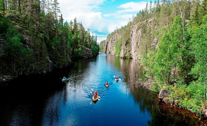 the wild taiga finland kayaking trip down a river amidst forests and rock cliffs