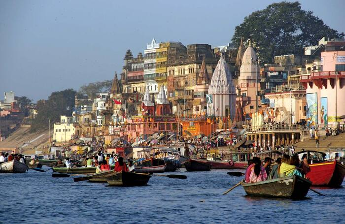 varnasi india river with boats and people tall colorful buildings on the coast