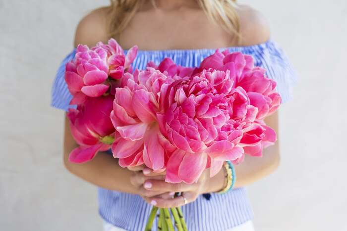 woman in light blue off shoulder top holding bright pink peonies