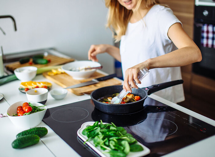 woman in white top cooking in a kitchen vegetable dish