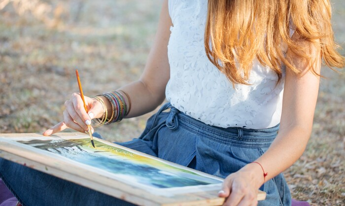 woman with long light hair in denim skirt and white top sitting outdoors painting
