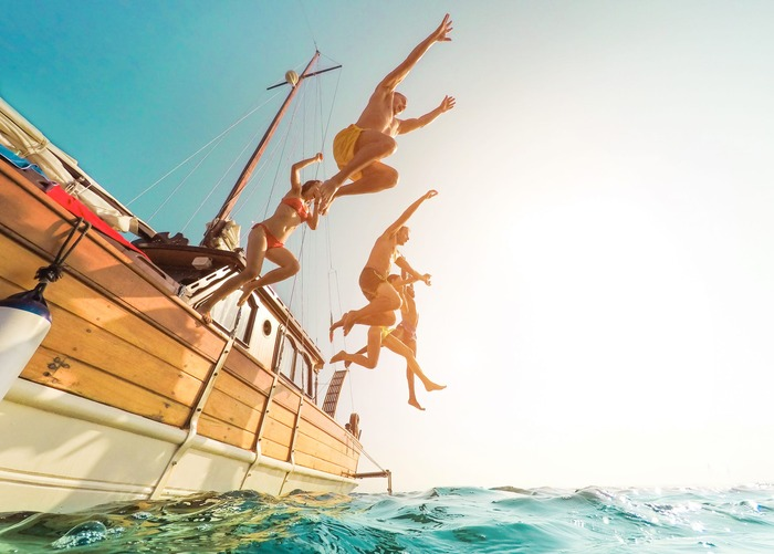 yachting journeys friends jumping in the water from a boat sea journeys yachting