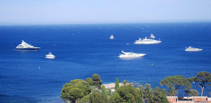 white yachts in a blue sea just off the coast