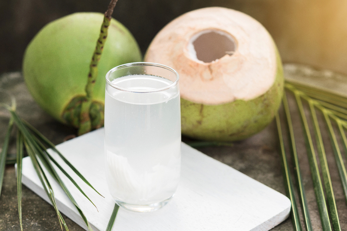 fresh coconut water full of minerals in a tall glass on a white plate with two open green coconuts in the background and palm leaves