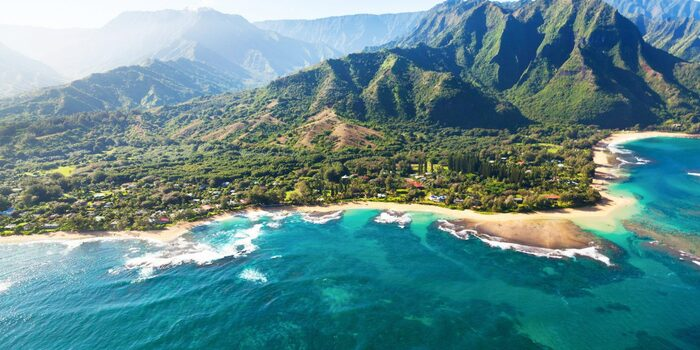 Kona Hawaii beach with crushing white waves and green coastline with high cliffs