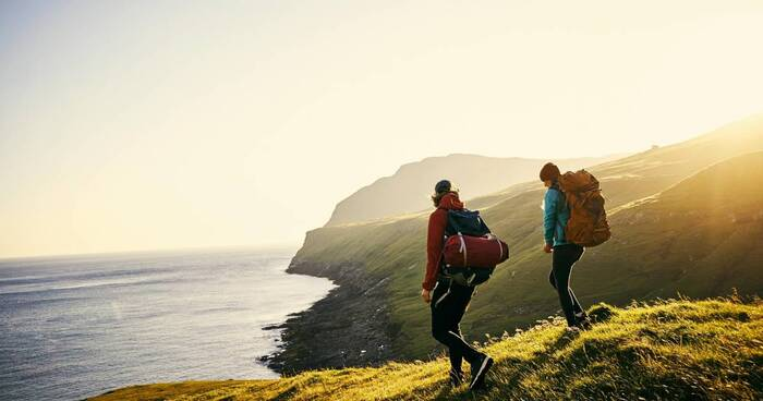 active vacations for couples couple hiking on grassy cliffs with the sea in the background
