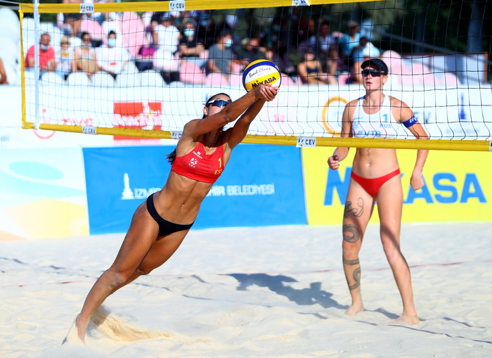 beach volleyball women playing on the beach in sports swimsuits hitting the ball close to the net