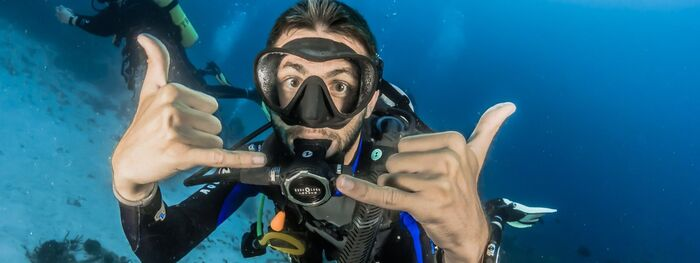 beginner scuba diver man in his diving costume showing a finger sign and looking into the camera deep underwater