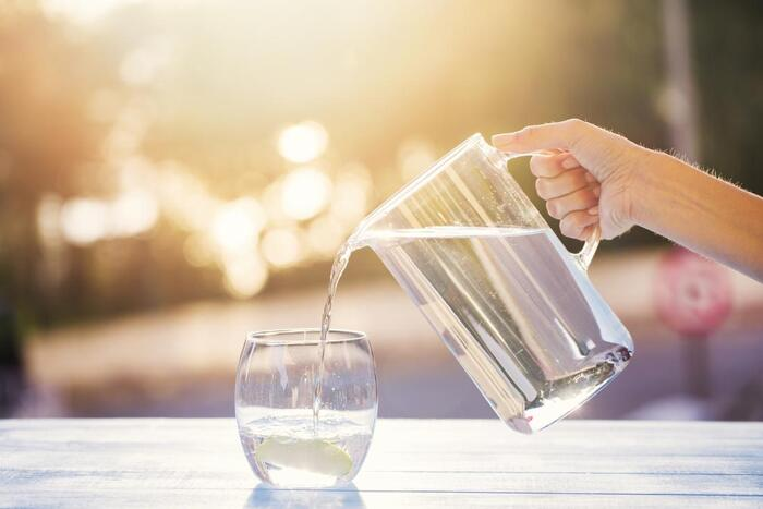 benefits of mineral water female hand pouring water from a large jug into a glass