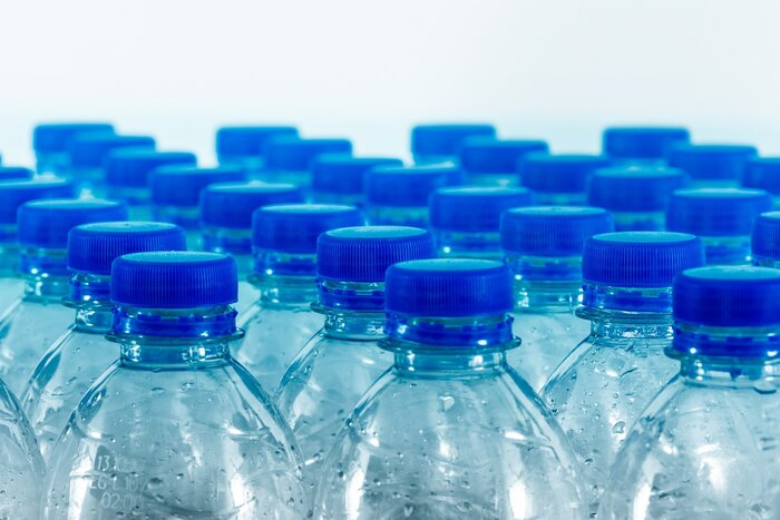 bottles of water with blue caps in several rows