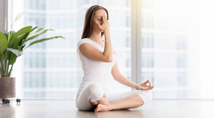 woman in white sitting on the floor in a yoga posture doing breathing exercises with her hand on her forehead