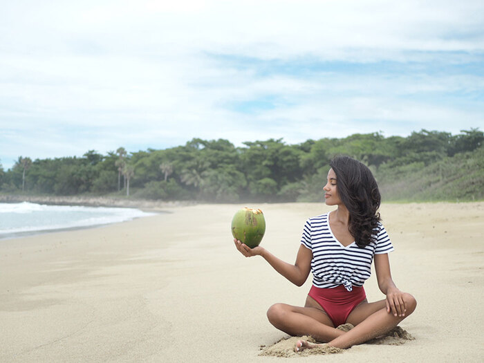 woman with dark hair and striped shirt sitting in a yoga pose on a wide breach holding a large green coconut in her hand