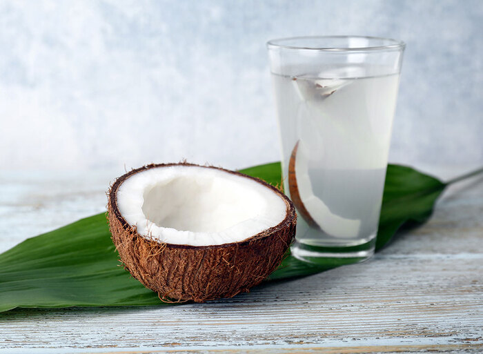 coconut water and half a coconut on a green leaf and grey table