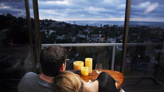 couple on a terrace cuddling and overlooking a sea town with the sea in the background candles on a table in front