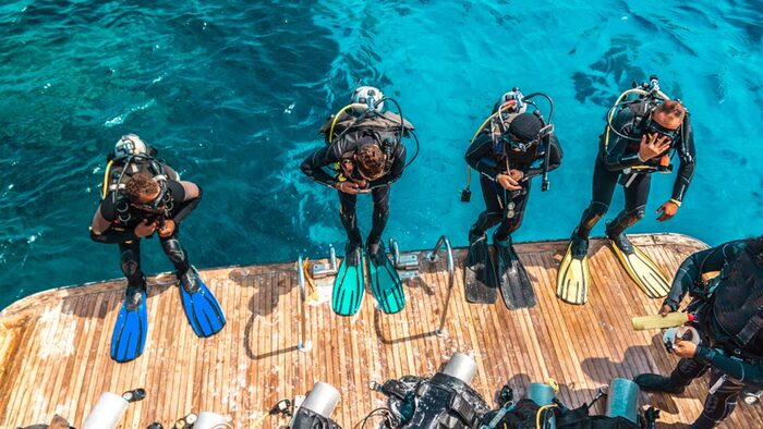 four divers ready and equipped to jump into the water from a deck