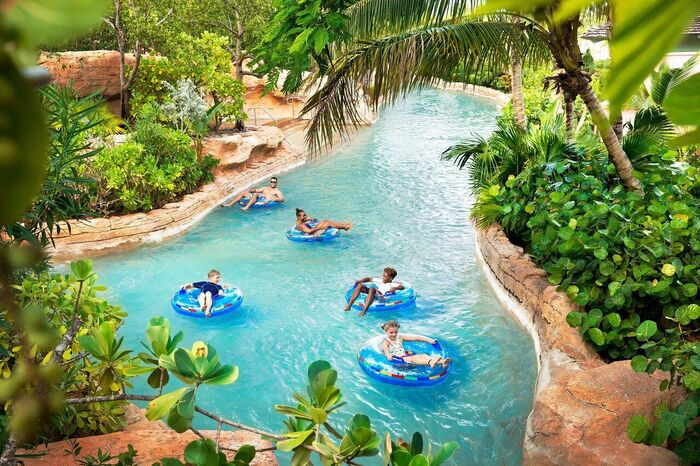 family activities in a long pool surrounded by tropical plants family members enjoying the ride