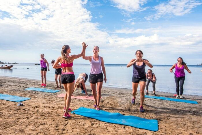 fitness vacation women on the beach with their mats working out