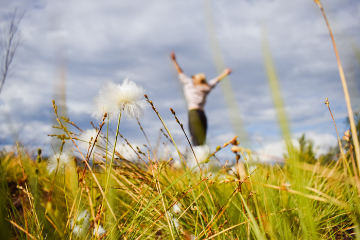 girl in nature jumping and having fun in the background close up of grass and flowers