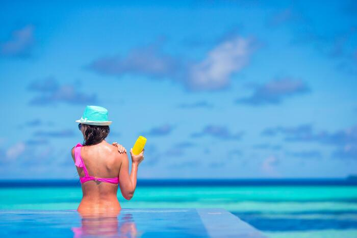 woman in a pool with pink swimsuit and bright blue hat applying sunscreen on her shoulder