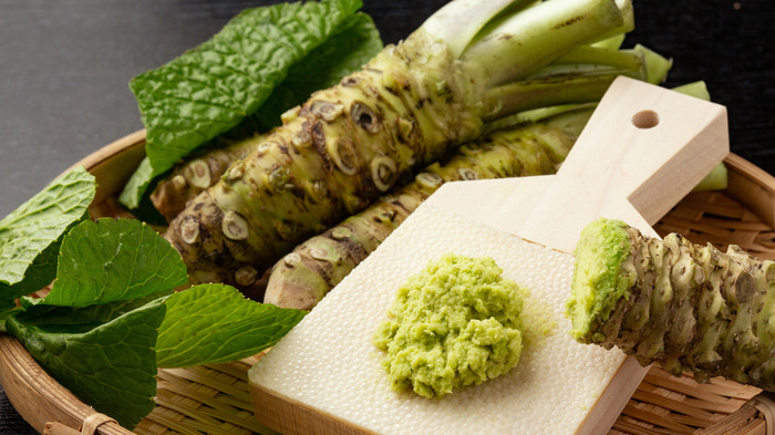 grated wasabi on a little wooden board wasabi roots in a basket with green wasabi leaves