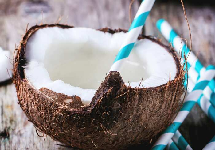 half coconut with a white and blue straw thick coconut milk inside