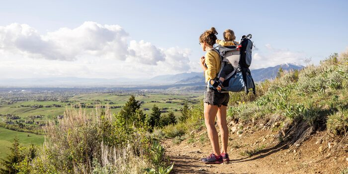 hiking with a baby women in shorts hiking with a baby on her back in a baby chair