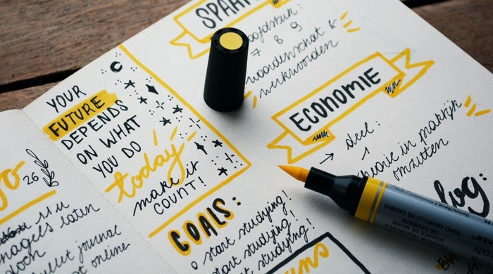 journaling notebook with a yellow pen and colorful journaling notes for goals and planning