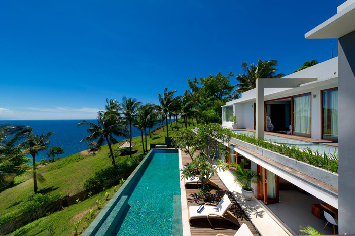 malibu cliff villa modern exterior long outdoor pool on a cliff with green grass and palm trees