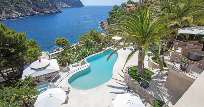 mallorca spain villa with an outdoor pool and a large palm tree overlooking the sea tropical landscape