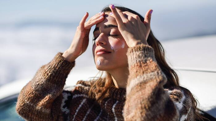 mountain sunscreen woman in a sweater applying sunscreen on her face with both her hands