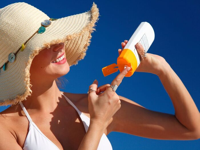 woman with a sun hat and white swim suit smiling and applying sun lotion from a bottle
