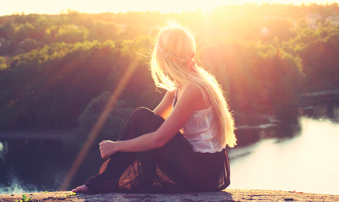 relax your mind woman with long blond hair sitting near the water looking at the sun raising and nature