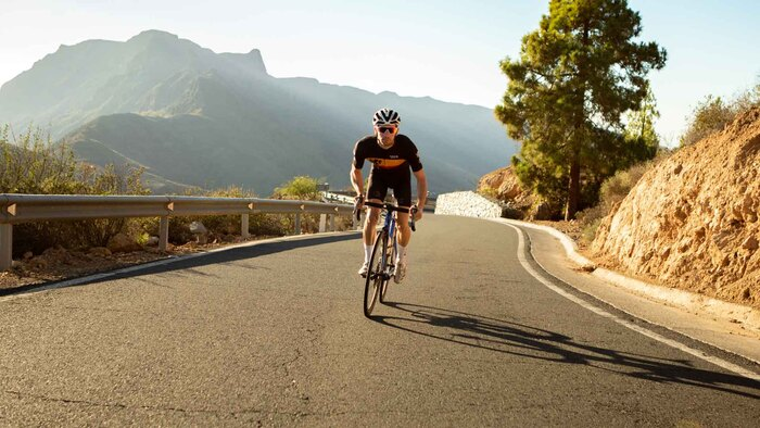 road cycling man on his bicycle cycling up a hill with cliffs in the background