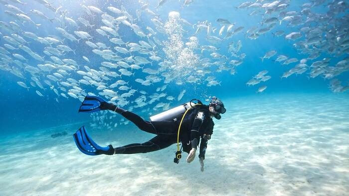 scuba diver in the maldives with a lot of little silver fish around him almost reaching the sandy bottom