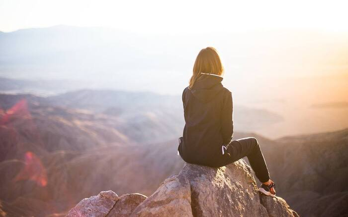 woman dressed in jacket and pants solo traveler sitting on a rock overlooking a hillside landscape at sunset