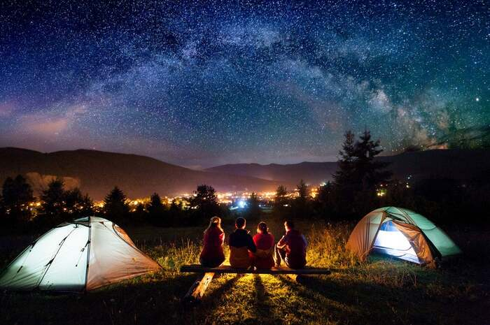 summer camping family sitting on a wooden bench between two tents overlooking the starry night around a fire