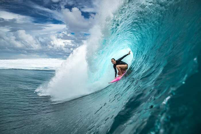 surfer in a large blue wave catching the wave summer sports