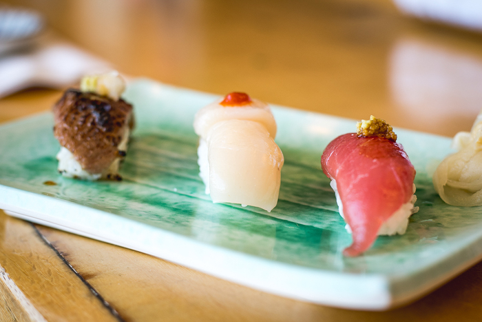 three pieces of sushi with fish on a green plate and a wooden table