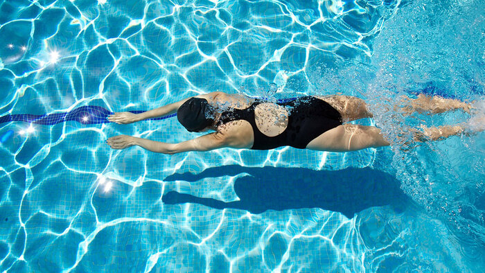 swimming summer sports woman in the water photographed from above in her black swimsuit
