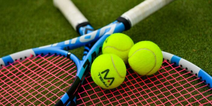 tennis balls and two rackets lying on the tennis ground