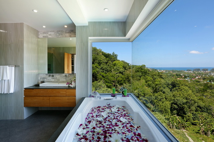 villa beyond phuket thailand bathroom with a view bathtub filled with rose petals next to a large window overlooking green landscape