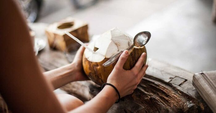 woman and coconut woman holding a spoon with a coconut with a straw in her hands on a wooden table