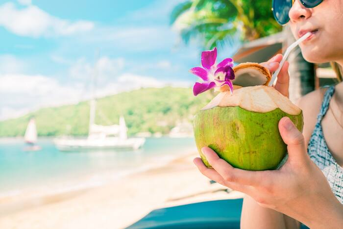 woman holding and drinking from a green coconut on a beach with a little purple flower on the coconut