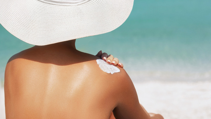 woman with a large white sun hat and bronze skin applying sunscreen on her shoulder while looking at the sea