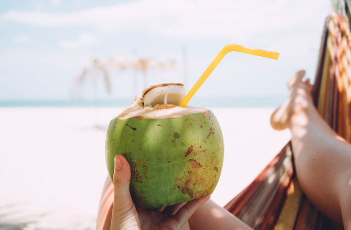 Woman lying on the beach holding a green coconut with a yellow straw in it relaxing and drinking coconut water