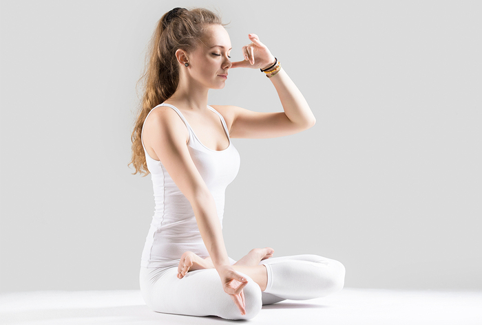 yoga breathing woman in white with long hair in a yoga posture doing breathing exercises