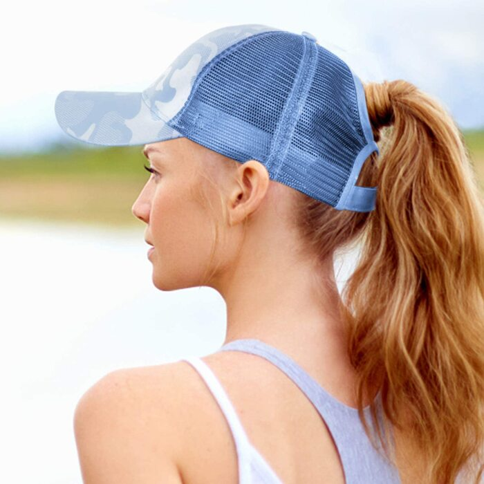woman with her back to the camera wearing a light blue baseball cap with her blond hair in a ponytail