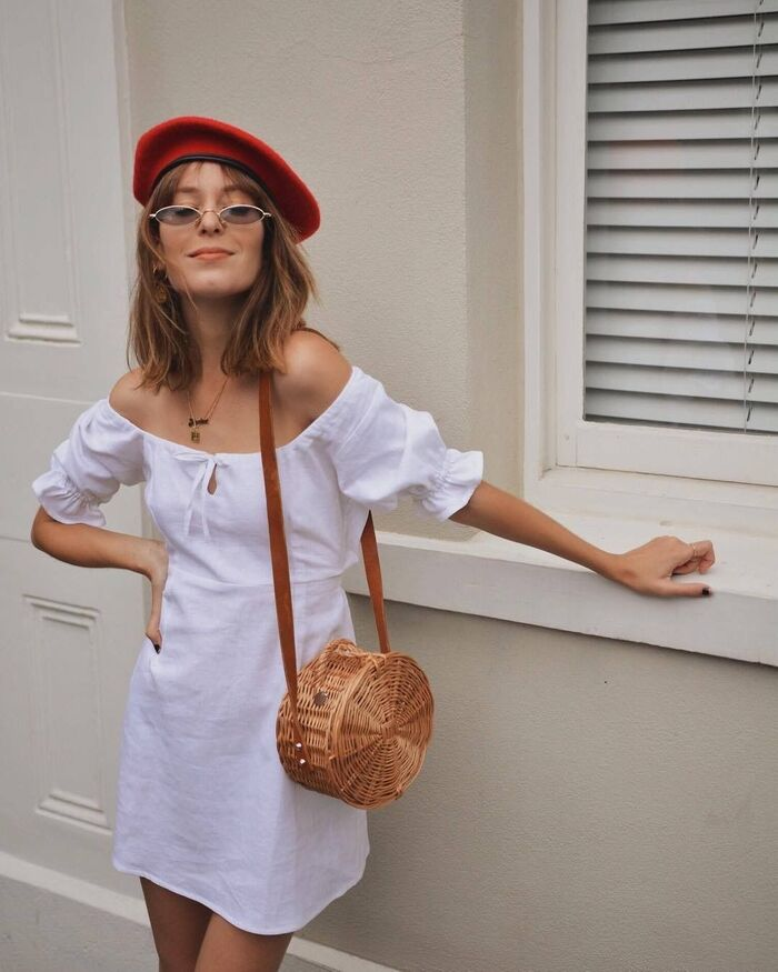 beret summer hat woman dressed in white with a red beret and glasses smiling at the camera